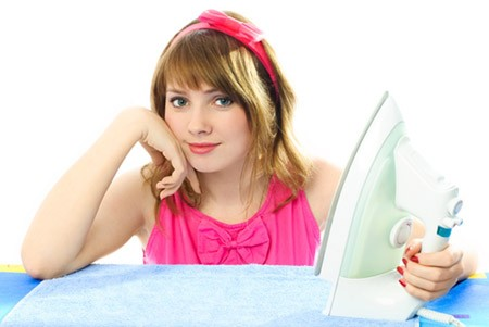 beautiful young woman dressed in pink retro clothes ironing towels