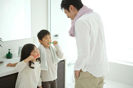 Father with his children brushing teeth