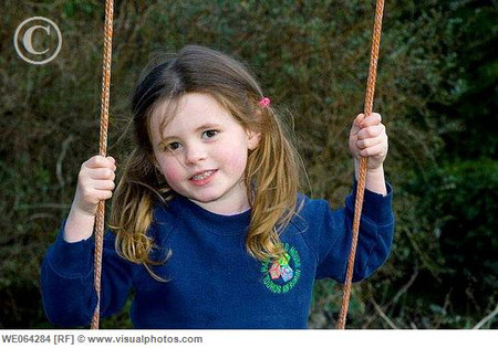4 year old girl swinging outside, wearing school uniform, with bunches