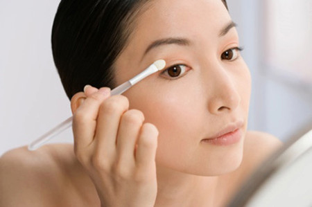 Asian woman applying eye shadow