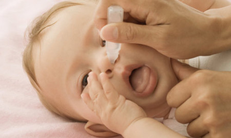 Dùng tăm bông hoặc khăn giấy mềm xoắn lại để lau khô mũi cho con.
