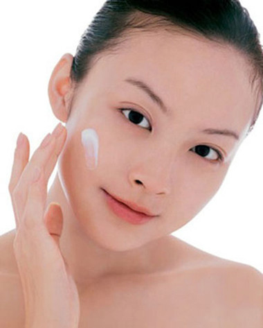 Young woman looking at camera, applying moisturizer on face
