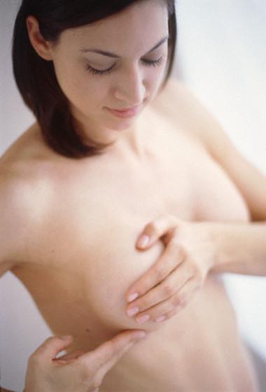 Naked Young Woman Examining Breasts