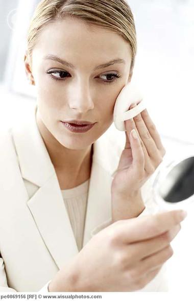 Businesswoman applying powder makeup